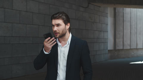 Businessman recording voice message on cellphone. Male manager using smartphone Live Action