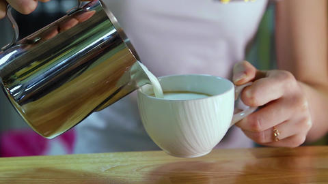 A girl pours milk from a shiny jug into a white cup. Close-up Live Action