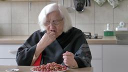 Old woman is eating red gooseberry Live Action