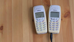 Two old Nokia 3410 Mobile phones on a table. Charging battery Live Action