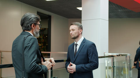 Business partners elegant men in formalwear discussing work in office lobby Live Action