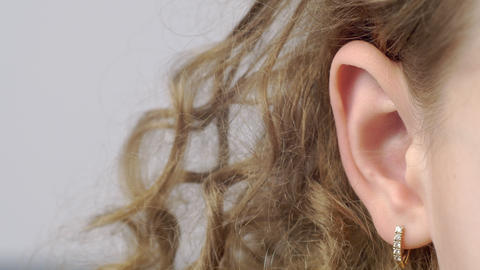 Closeup female ear with earrings front view. Right ear of curly young woman on GIF