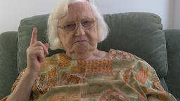 Displeased old woman is waving finger Live Action
