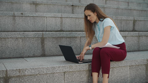 Businesswoman working on laptop outside. Executive typing on laptop at street Live Action