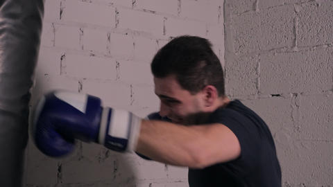 Brutal boxer in gloves punching combat bag in boxing club. Sportsman training GIF