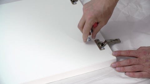 Close up male hand tightens screw with screwdriver on furniture hinge during GIF