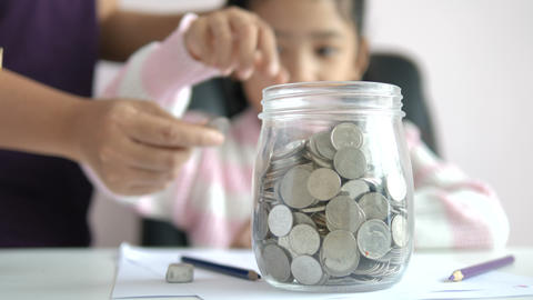 Mother and little Asian girl putting the coin into clear glass jar Live Action