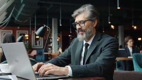 Mature entrepreneur using laptop computer in restaurant typing at table alone Live Action