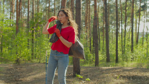 Asian female eco activist carrying garbage bag Live Action