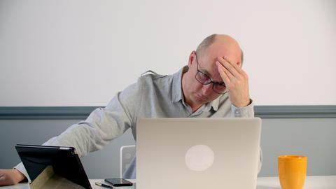 Depressed man touching forehead while hard work on laptop in office. Tired man Live Action