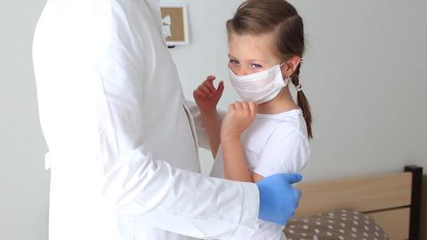 Doctor hugs a little girl in a respiratory mask Acción en vivo