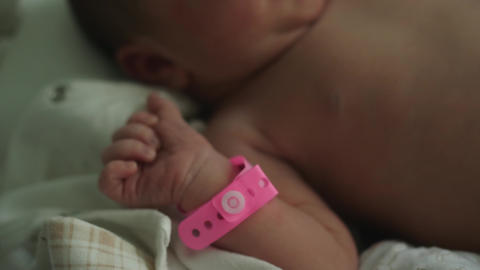 infant newborn hand arm wrist pink girl band hospital identification wristband Live Action