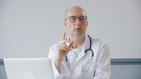 Professional doctor talking with patient and looking at camera Live Action