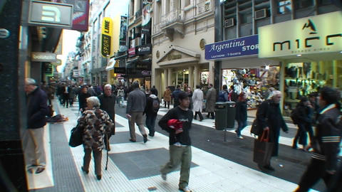 People walk through a city shopping area Stock Video Footage