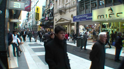 People walk through a city shopping area Footage