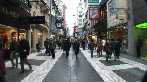 Shoppers walk down a crowded busy street Footage