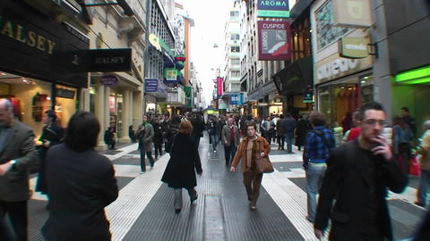 Shoppers walk down a crowded busy street Stock Video Footage