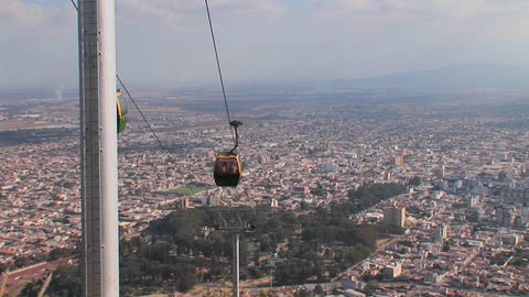 People are transported via cable car high above a city Stock Video Footage