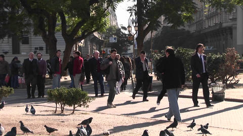 Crowds of people walk across a street and through a small... Stock Video Footage