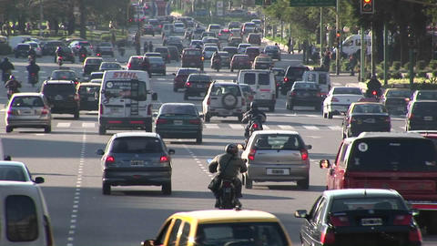 A city street is packed with cars, motorcycles and a few pedestrians Footage