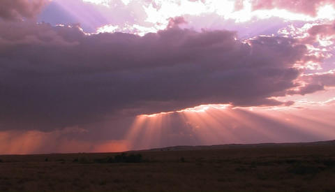 Beautiful sun beams burst forth from dark clouds onto open plains Footage