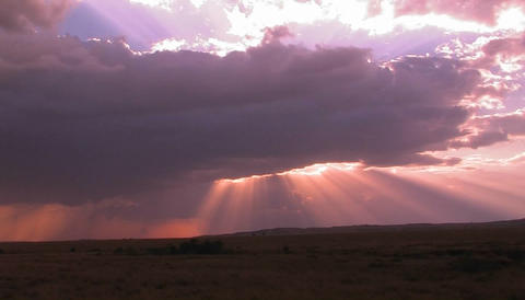 Beautiful sun beams burst forth from dark clouds onto... Stock Video Footage
