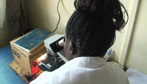 A technician is viewing a specimen through a microscope Stock Video Footage