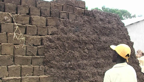 A man throws handfulls of daub on a mud bricked wall Stock Video Footage