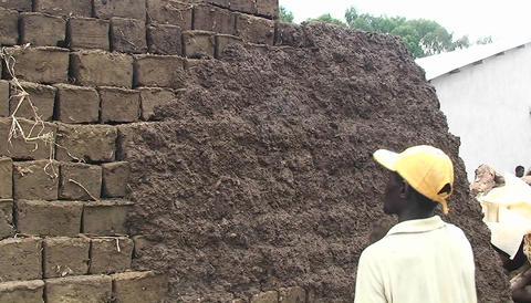 A man throws handfulls of daub on a mud bricked wall Stock Video Footage