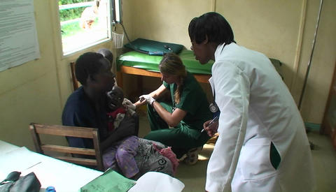 Sick children are getting a check-up by two doctors at a clinic Footage