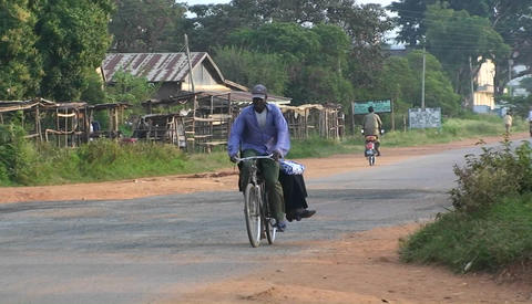 People ride bicycles and walk along a road in an African... Stock Video Footage