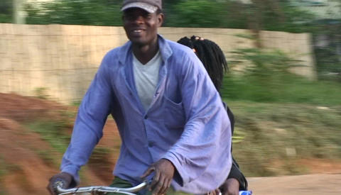 People ride bicycles and walk along a road in an African village Footage