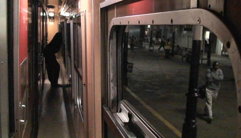 A person stands looking out the window as the train... Stock Video Footage