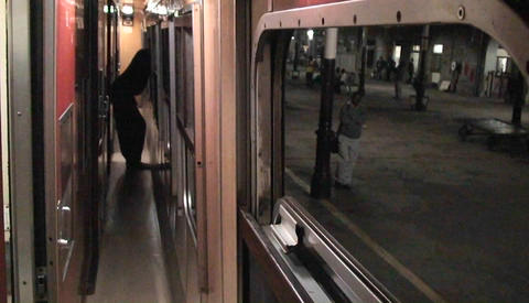 A person stands looking out the window as the train leaves the station, and a man walks along on the Footage
