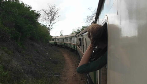 A woman sticks her head out the window letting her hair blow in the wind, then turns, smiles and put Footage