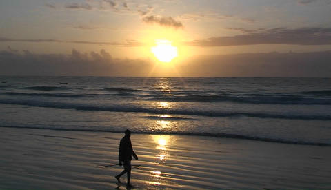 A man walks along the beach carrying a stick as the waves come in and the sun sets Footage