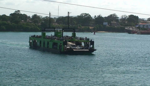 A ferry boat carries people and vehicles across a body of... Stock Video Footage