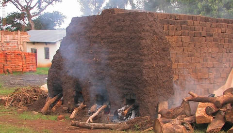 Smoke billows as bricks are fired at a construction site in rural Africa Footage