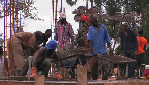 A construction crew works on pouring concrete for a building Stock Video Footage