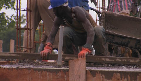 A construction worker uses a long board to screed concrete Stock Video Footage