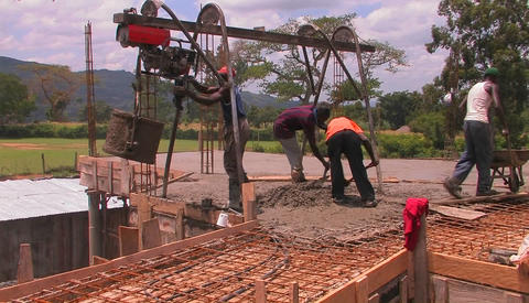 Workers fill a wheel-barrel up with fresh concrete Footage