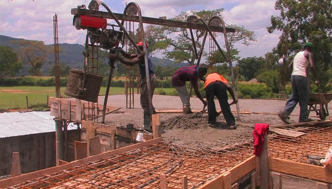 Workers fill a wheel-barrel up with fresh concrete Stock Video Footage