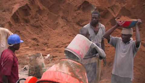 Men throw cement and aggregate into a cement mixer Stock Video Footage