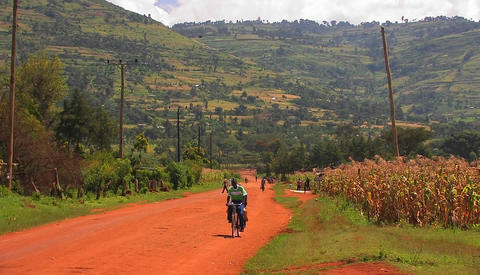 Two Africans ride on a bike down a red dirt road Stock Video Footage