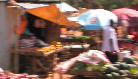 People buy produce at stands, cars pass by on the street Stock Video Footage