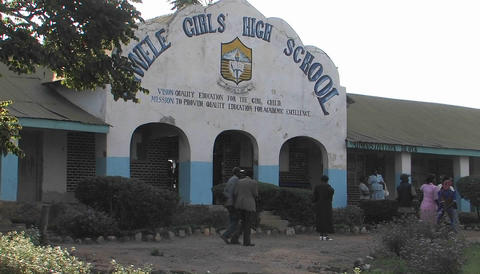 People walk past a highschool in Africa Stock Video Footage