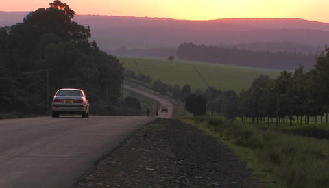 Vehicles travel a rural highway near sunset Stock Video Footage