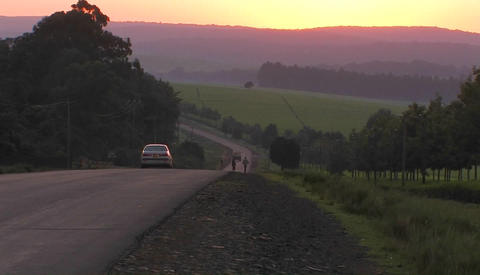 Vehicles travel a rural highway near sunset Footage