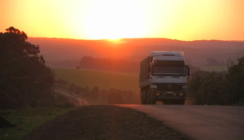 A truck travels down a rural highway near sunset Footage