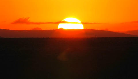 The sun rises on the horizon behind low hills Stock Video Footage